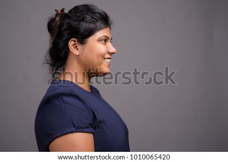 Studio shot of young overweight beautiful Asian woman against gray background