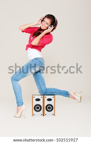studio shot of young woman in headphones over grey background