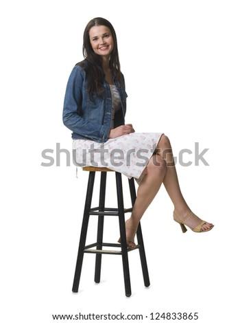 Studio shot of young woman sitting on bar stool