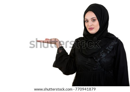 studio shot of young woman wearing traditional arabic clothing. she's holding her hand to the side