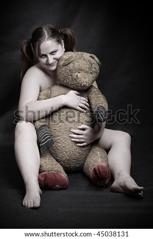 Studio shot overweight woman with old Teddy bear. Great for calendar.