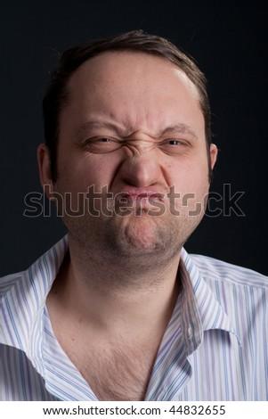 studio shot portrait of a young funny expressive crazy man