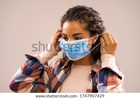Studio shot portrait of beautiful african-american ethnicity woman who is putting protective mask. ストックフォト ©