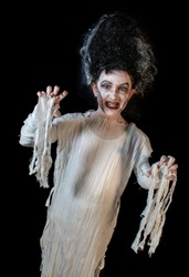 studio shot portrait of young girl in costume dressed as a Halloween, cosplay of scary bride of Frankenstein pose on isolated black background