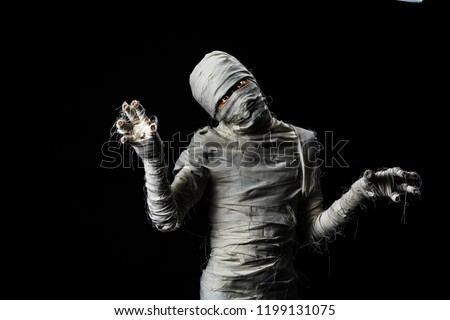 Studio shot portrait of young man covered by cloths in costume dressed as a halloween cosplay of scary mummy pose  acting on isolated black background.
