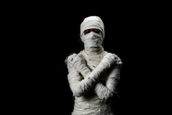 Studio shot portrait  of young man in costume  dressed as a halloween  cosplay of scary mummy pose like close eye and cross his arm acting standing on isolated black background.