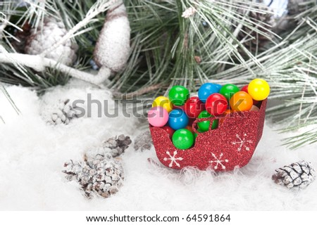 Studio shot setting of a Christmas sleigh filled with colorful holiday gumballs set in a snowy, pine tree background.