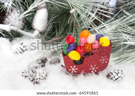 Studio shot setting of a Christmas sleigh filled with colorful holiday jelly beans set in a snowy, pine tree background.