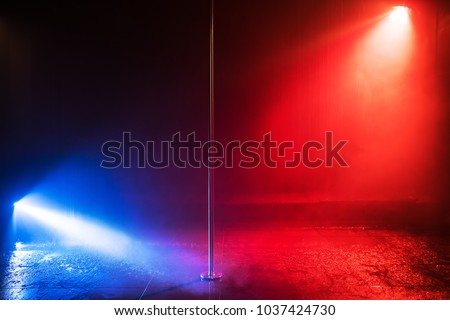 Studio stage with pole for dancing in center. Blue and red lights. Water effect. #1037424730