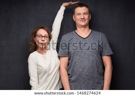 Studio waist-up shot of amazed short woman pulling up and showing with hand at height of tall man standing beside her, smiling and looking at camera, over gray background. Variety of person