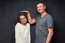 Studio waist-up shot of tall man smiling and showing with hand at height of short girl standing beside him and looking with perplexity at camera, over gray background. Variety of person's heights