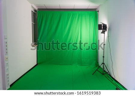 Photo of  Studio with a green screen and a video light illuminating the green screen