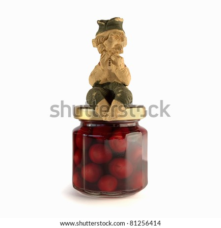 Studio work of a bottle with cherries and a figure of Serbian man playing music instrument called Frula.