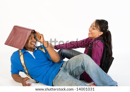 Studious, attractive teen couple flirting.  The young man is lounging on the ground with a folder on his head.  The young woman, who is sitting on the ground, is looking at him laughing.