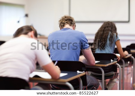 Studious young adults writing in a classroom