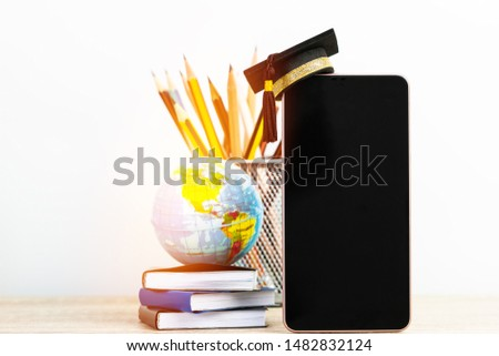 Study abroad education in modern technology global business or online learning.Mortarboard graduation cap on blank screen smartphone, globe on stack books on background. E-learning Graduated in school