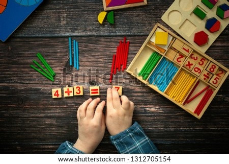 study of mathematics and mathematical calculation with the help of wooden manuals. The child decides an example, studies fractions. Wooden background, top view