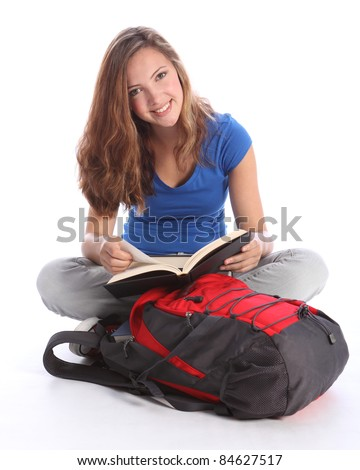 Study time for beautiful high school teenage student girl reading education book sitting cross legged on floor, with school rucksack wearing blue t-shirt, jeans and red sneakers.