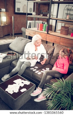 Study with granny. Top view of smart preschool girl studying letters with her caring granny