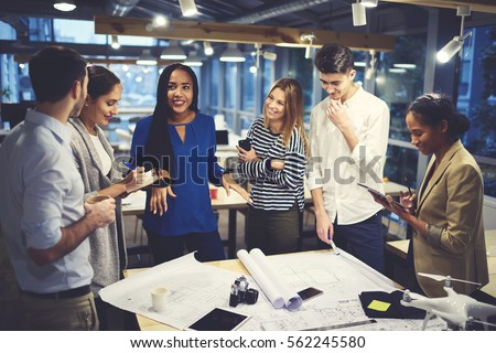 Studying group of male and female designers working in friendly atmosphere creating map of city landscape under orders from skilled leader using wireless connection to internet and modern technologies