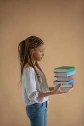Studying process. Disappointed young African American female carrying pile of books in front of her