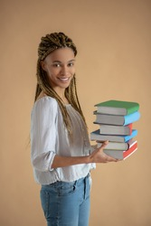 Studying process. Happy young African American female carrying pile of books in front of her, smiling