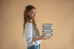 Studying process. Happy young African American female carrying pile of books in front of her