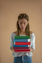 Studying process. Upset young African American female carrying pile of books