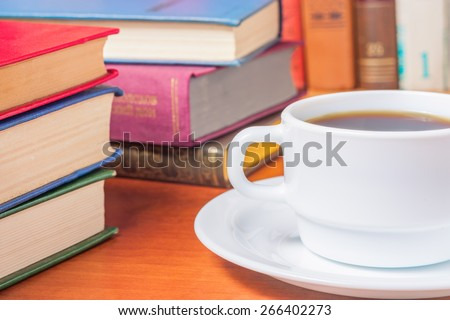 Studying scientific literature in the library with and drinking coffee