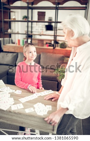Studying with granny. Dark-eyed girl wearing pink shirt standing neat table and studying with granny