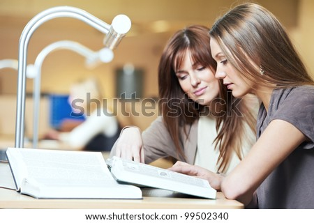 Studying young teenage college student girl  in a library with books in front of book shelves