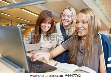 Studying young teenage college student girl in a library with Laptop computer