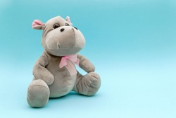 Stuffed animal hippo on blue background. Child soft toy, comforter for sleep.
