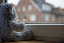 Stuffed animal looking out of a window, symbolizing isolated children during lockdown or quarantine during the corona pandemic