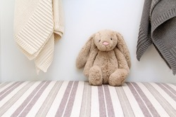 Stuffed animal sitting on a shelf in a baby's room. Toy bunny rabbit.