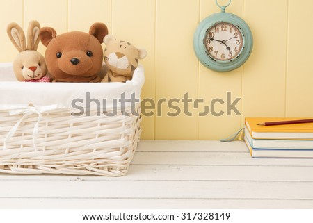 Stuffed animal toys in a basket and a blue clock on the wainscot. Some notebooks and a pencil. Back to school.