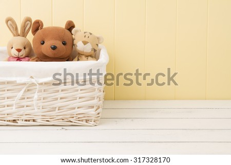 Stuffed animal toys in a basket on the floor