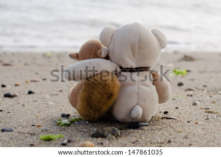 Stuffed animals sitting in the sand looking at the ocean