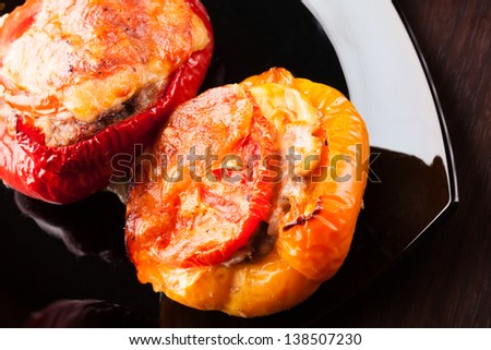 Stuffed bell peppers with chopped meat, cheese and tomato on black plate