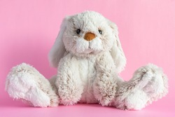 Stuffed bunny on pink background. Easter concept. Cute toy bunny sitting on colored background.