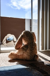 stuffed bunny with a face mask in self isolation looking outside