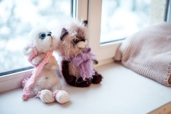 Stuffed cats sit on the window. Handmade plush toys. Games and recreation with baby toys.