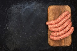 Stuffed Chorizo Sausages on Wooden Cutting Board and Black Table Background, Top View. Raw Sausages In Natural Casing. Cookout Food. Uncooked Sausages On Cutting Board, Overhead View.