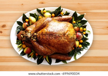 Stuffed cooked turkey with garnishes on a wood table. Top-view, flat-lay