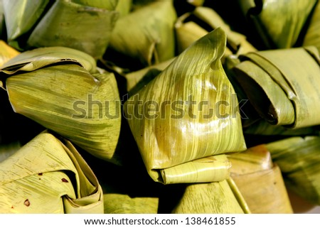 stuffed dough pyramid dessert made from sticky rice flour and palm sugar wrapped with banana leaf in pyramid shape