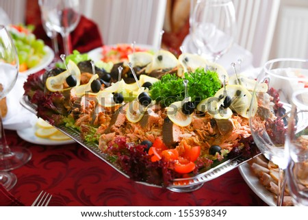 Stuffed fish on a banquet table. Cut into pieces and decorated with vegetables
