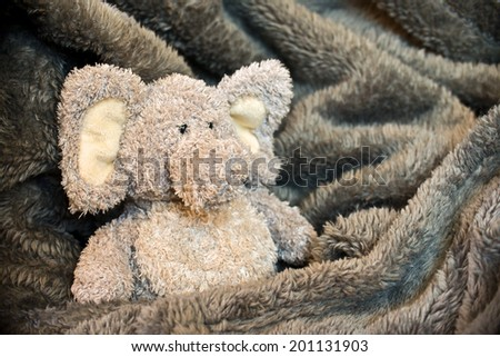 Stuffed fluffy animal in a soft blanket