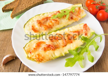 Stuffed fresh homemade zucchini with tomatoes, garlic and cheese on wooden background with argula leaves and bread, close up, horizontal. Natural vegetarian dinner concept.