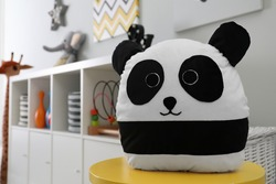 Stuffed panda toy on table in child's room. Space for text