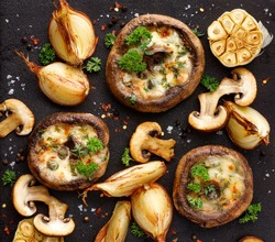 Stuffed portobello mushrooms stuffed with mozzarella and gorgonzola cheese and aromatic herbs on a black background, top view. Vegetarian food